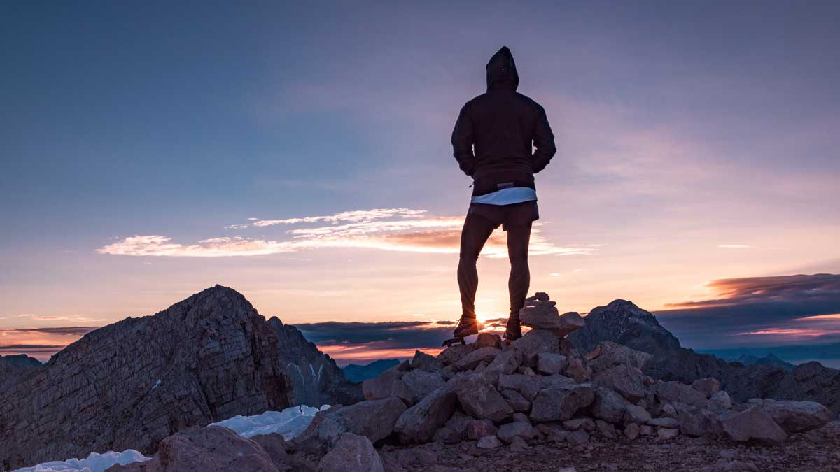 Man on top of mountain sunrise